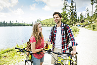Young couple taking a break on a bicycle trip - HAPF00849