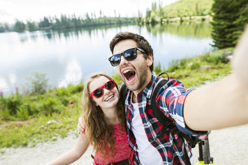 Young couple taking selfies on a bicycle trip - HAPF00855