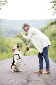 Senior woman teaching her dog - HAPF00882