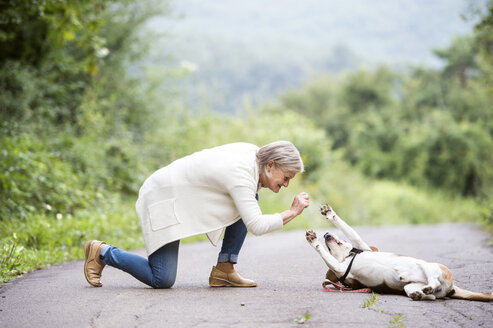 Senior woman with her dog in nature - HAPF00885