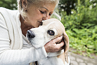 Happy senior woman cuddling her dog - HAPF00888