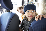 Little boy sitting in car with brothers - FSF00449