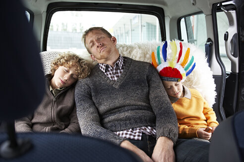 Sleeping father sitting in car on back seat with his sons - FSF00452