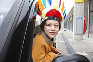 Boy with feather headdress looking out of car window - FSF00455