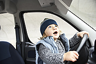Little boy sitting at steering wheel of car - FSF00458
