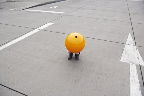 Little girl crouching in street, hiding under orange sphere - FSF00488