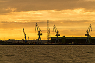 Germany, Stralsund, view to silhouettes of harbour cranes at shipyard by twilight - TAMF00651