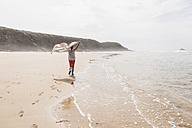 Mature woman walking on the beach lifting a blanket - UUF08563