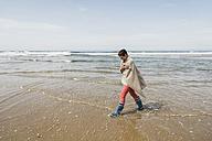 Mature woman walking on the beach - UUF08566