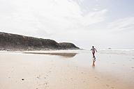Mature woman running on the beach - UUF08569