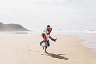 Happy mature man carrying wife piggyback on the beach - UUF08575