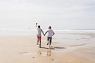 Mature couple running on the beach - UUF08578