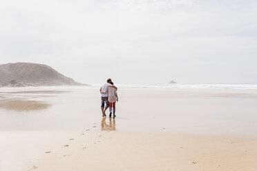 Mature couple walking on the beach - UUF08581