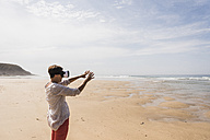 Mature woman standing on the beach wearing VR glasses - UUF08584