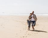Mature couple walking on the beach - UUF08593