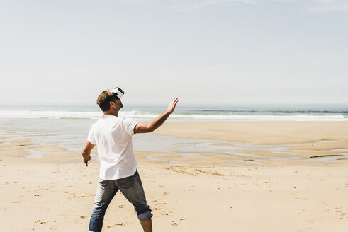 Mature man standing on the beach wearing VR glasses - UUF08596