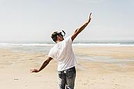Mature man standing on the beach wearing VR glasses - UUF08599