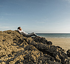 Mature woman relaxing on rock at the beach - UUF08602