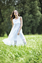 Happy woman wearing white summer dress standing on a meadow - MAEF12021