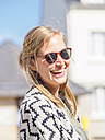 Portrait of happy young woman wearing sunglasses - LAF01736