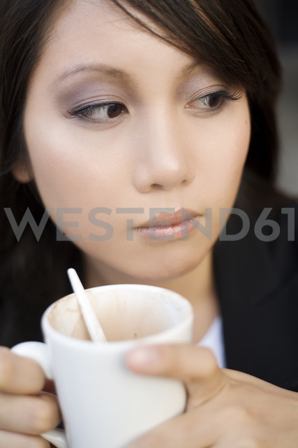 Young woman with cup of coffee watching something - NGF00364 - Nadine Ginzel/Westend61