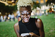 Young woman sitting in a park at night looking at cell phone - GIOF01464