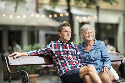 Senior couple sitting on bench watching something - HAPF00892