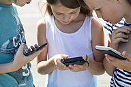 Three children with smartphones - SARF02904