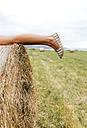 Legs of teenage girl lying on straw bale - MGOF02438
