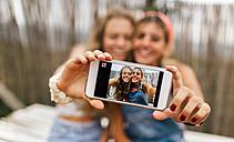 Selfie of two smiling teenage girls on display of smartphone - MGOF02444
