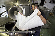 Man pouring a bag of malt in a beer tank in a factory - ABZF01241