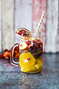 Glass of infused water with orange slices, fig, pomegranate seed, nectarine and plums - SARF02908