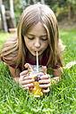 Girl lying on a meadow drinking infused water with various fruits - SARF02911