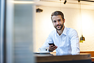 Portrait of smiling businessman with cell phone in a cafe - DIGF01232