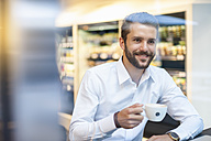 Smiling businessman with cup of coffee in a cafe - DIGF01238