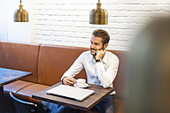 Smiling businessman sitting in a cafe with cup of coffee - DIGF01241