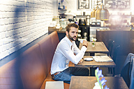 Businessman sitting in a cafe with cup of coffee - DIGF01247