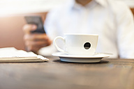 Close-up of businessman cup of coffee with businessman on cell phone in background - DIGF01250
