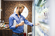 Young man choosing food from cooling shelf in a coffee shop - DIGF01289