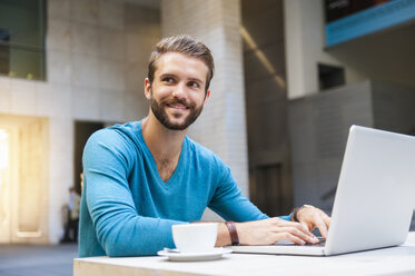 Smiling young man sitting at table using laptop - DIGF01295