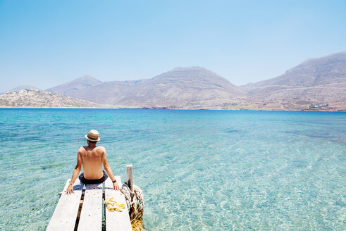 Greece, Cyclades islands, Amorgos, man sitting on the edge of a wooden pier, Nikouria island - GEMF01020