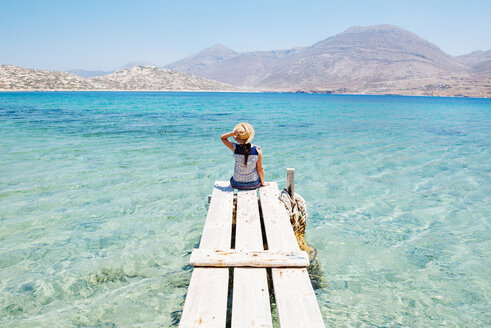 Greece, Cyclades islands, Amorgos, woman sitting on the edge of a wooden pier, Nikouria island - GEMF01023