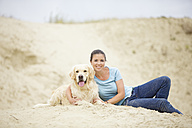 Smiling young woman with dog in sand - MAEF12031