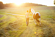 Young woman with horse in rural landscape at sunset - MAEF12042