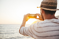 Greece, Cylcades Islands, Amorgos, man taking pictures of the sunset with a smartphone next to the sea - GEMF01033