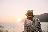Greece, Cylcades Islands, Amorgos, man enjoying the sunset next to the sea - GEMF01039