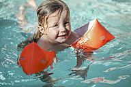 Little girl with floating tire in swimming pool - SHKF00674