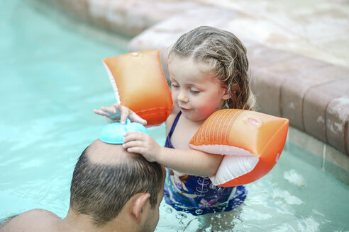 Father and little daughter playing together in swimming pool - SHKF00680