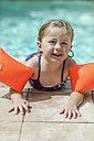 Portrait of little girl with floating tire at  pool edge - SHKF00683