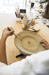 Woman decorating a plate in a ceramics workshop - ABZF01249